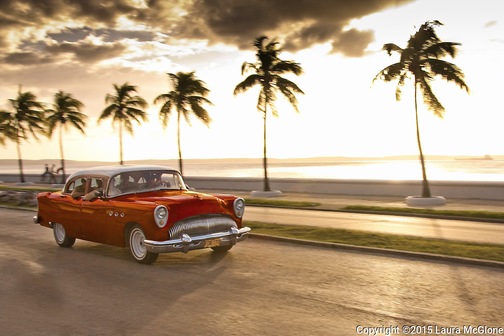 Cuba - Red 1950s car speeding along roadway with palm trees in background