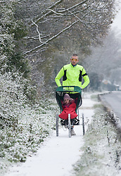 © under license to London News pictures. 27/11/2010. A man goes for a run with his daughter in the snow in Clifton, Bedfordshire this morning (27/11/2010). The whole of the UK is expected experience sub zero temperatures and heavy snowfall over the next few weeks. Photo credit should read: Stephen Simpson/LNP