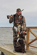 Successful waterfowl hunter with his young Labrador and a strap full of ducks.
