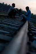 Two men sit and chat on the railroad tracks that lead through Chittagong, Bangladesh.