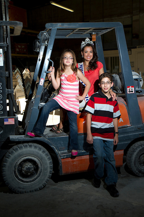 Mrs. America April Lufriu with her two children Brandon and Savannah at the family business. Her kids are the reason why she ran in the pageants-- to raise awareness for retinitis pigmentosa, a genetic eye disease that leads to blindness-- a condition they all three have.  ..Photo by James Branaman