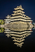 "Matsumoto Castle, built 1592-1614, lit at night reflecting in moat, in Nagano Prefecture, Japan. The castle was built from 1592-1614 in Matsumoto, Nagano Prefecture, Japan. Matsumoto Castle is a ""hirajiro"" - a castle built on plains rather than on a hill or mountain, in Matsumoto. Matsumotojo's main castle keep and its smaller, second donjon were built from 1592 to 1614, well-fortified as peace was not yet fully achieved at the time. In 1635, when military threats had ceased, a third, barely defended turret and another for moon viewing were added to the castle. Interesting features of the castle include steep wooden stairs, openings to drop stones onto invaders, openings for archers, as well as an observation deck at the top, sixth floor of the main keep with views over the Matsumoto city."
