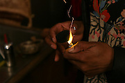 BROOKLYN, NY, APRIL 2, 2016:  Karen Rose, owner and head herbalist at Sacred Vibes apothecary in Ditmas Park, lighting a piece of charcoal on which to burn some resin to clear the energy of the room.  04/02/2016 (Kazi Awal/NYCity News Service)