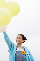 Smiling Pre-teen standing arms raised Holding Balloons