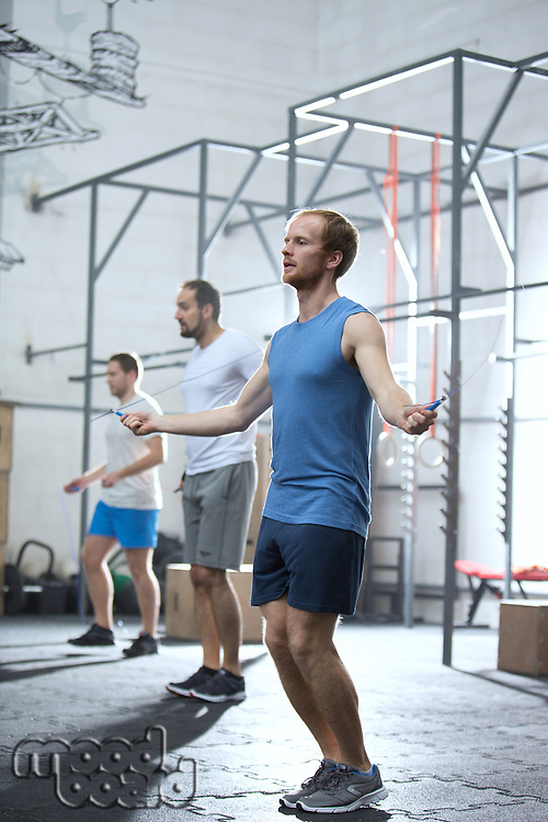 Full-length of men exercising in crossfit gym