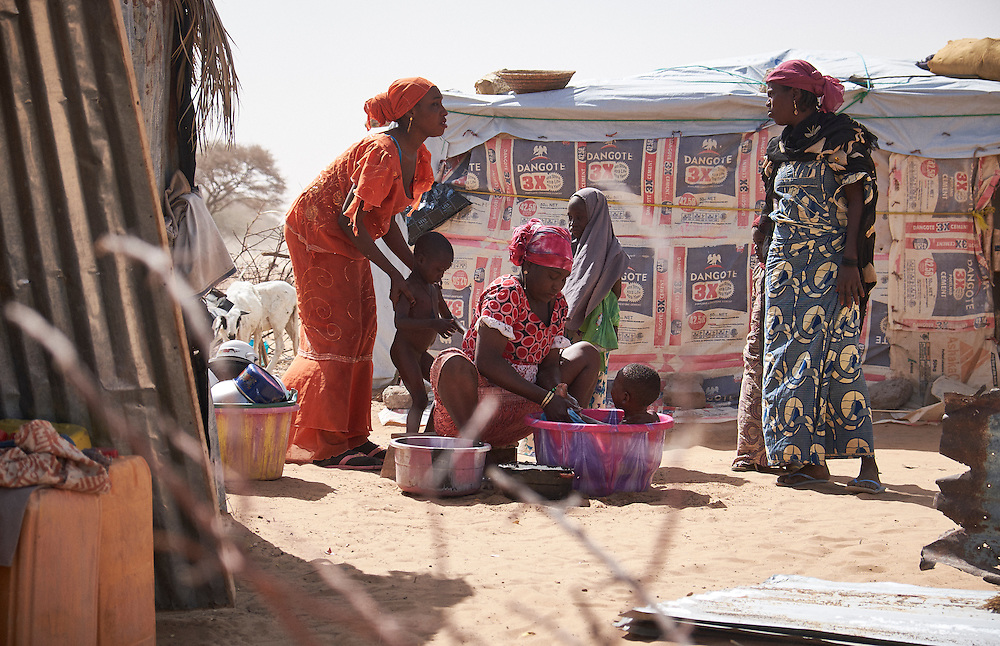 Women wash children in the village of Guidan Kaji near the border with Nigeria on the outskirts of Diffa, Niger on February 13, 2016. Displaced people from Niger and Nigeria are sheltering in the village after fleeing at the nearby border. Many of the families had witnessed attacks by Boko Haram in their villages or had fled because of other villages around them being attacked. Caritas undertook a distribution of sleeping covers, mosquito nets, pots and money transfers.