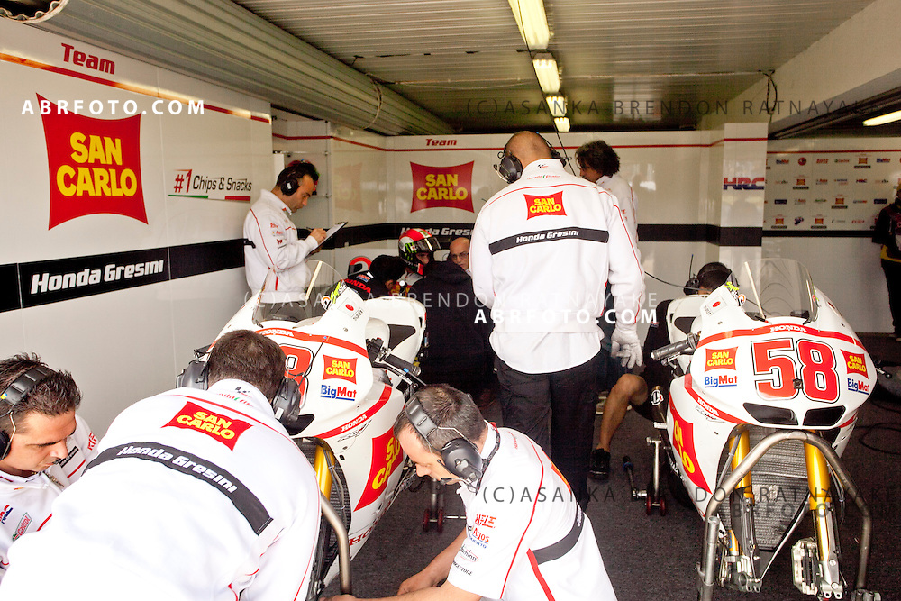 15 October 2011: 2011 The San Carlo Honda Gresini pit crew working on their riders bikes with Marco Simoncelli (58) in the background talking to his engineers him during Moto Gp qualifying at the Phillip Island Circuit in Phillip Island, Victoria, Australia.