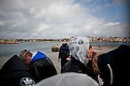 LAMPEDUSA. UN CARABINIERE CONTROLLA IMMIGRATI TUNISINI SULLA BANCHINA DEL PORTO DI LAMPEDUSA IN ATTESA DI ESSERE TRASFERITI IN SICILIA CON UNA NAVE PASSEGGERI;