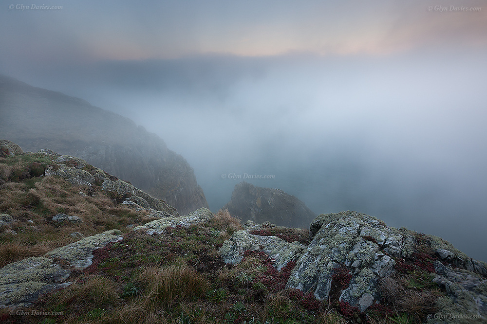 Thick fog at sunset, caused by a major temperature inversion, seen here at the high cliffs at South Stack, Holy Island, Irish Sea, North Wales.