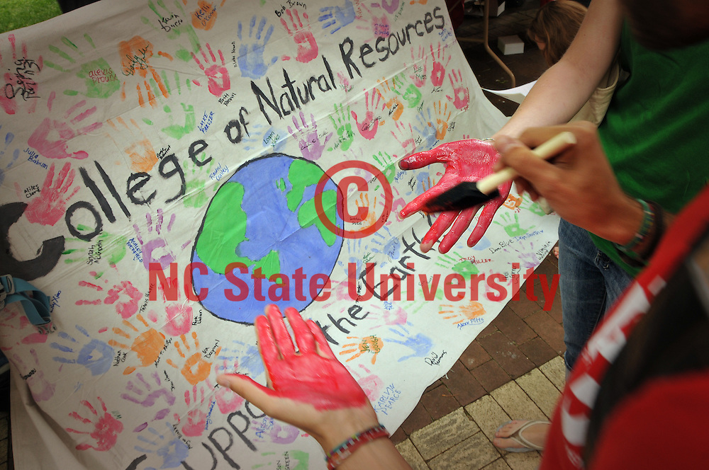 Students paint their hands to decorate a CNR banner during Earth Day activities on the Brickyard.