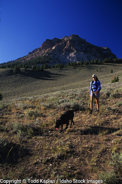 Idaho. Woman and her dog hiking in Boulder Mountains. MR