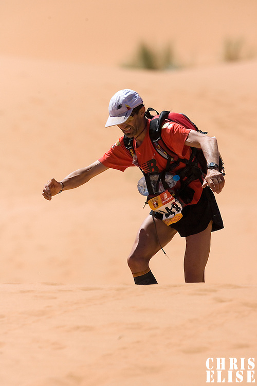 30 March 2007: #348 Gilles Fricotteaux of France climbs a dune in erg Znaigui en route to check point 3 during fifth stage of the 22nd Marathon des Sables between west of Kfiroun and erg Chebbi (26.22 miles). The Marathon des Sables is a 6 days and 151 miles endurance race with food self sufficiency across the Sahara Desert in Morocco. Each participant must carry his, or her, own backpack containing food, sleeping gear and other material.