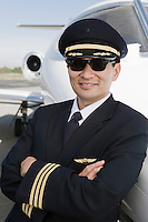 Portrait of Asian male pilot in front of private jet.