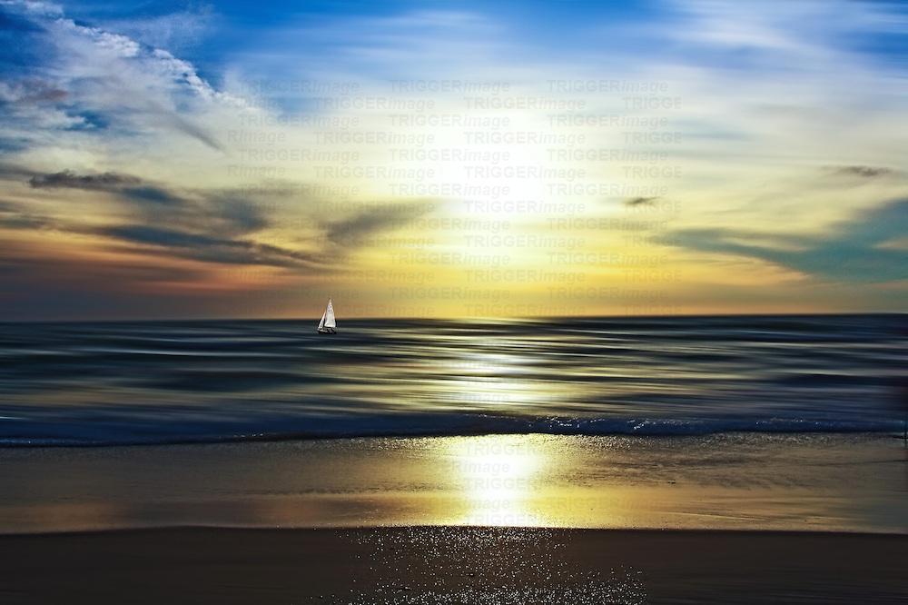 Conceptual beach scene with sail boat on sea