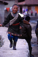 A young Tibetan nomad boy running along a wall in Langmusi, China.