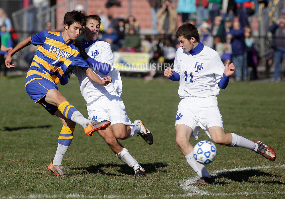 Middletown, New York - Lansing's Woojin Richardson, left, takes a shot under pressure from Evan Phillips and Justin Gaines (11) of Hoosick Falls during a Class C state semifinal boys' soccer game at Faller Field in Middletown on Saturday, Nov. 17, 2012.