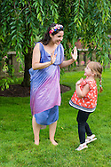 Old Westbury, New York, USA. 28th June 2015. Lori Belilove & The Isadora Duncan Dance Company, dressed in Renaissance themed tunics, give dancing lessons to children throughout the gardens, and then perform at historic Old Westbury Gardens, a Long Island Gold Coast estate, for its Midsummer Night event. A member of the dance company smiles and gives double high-five to smiling young girl dancing.