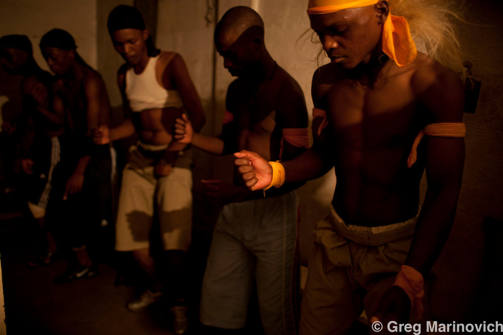 Traditional Zulu Mzansi dancers from Bergville practice then dance by candlelight inside the Zulu-dominated Madala hostel in the tiny impoverished township of Alexandra in Johannesburg is alongside Sandton, the ultra wealthy business hub of South Africa. Photo Greg Marinovich