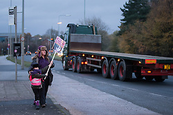 © Licensed to London News Pictures . 27/11/2013 . Manchester , UK . A woman and a young girl wave a placard at lorries leaving the site . Energy firm IGas have today (Wednesday 27th November 2013) been receiving drilling equipment in readiness for exploratory drilling at the site . Anti fracking protesters have established a camp at Barton Moss in Greater Manchester alongside an access road leading to an IGas drilling site .  Photo credit : Joel Goodman/LNP