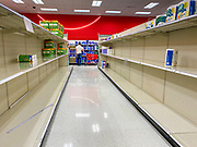 "15 MARCH 2020 - ALTOONA, IOWA: Customers walk through the stripped bare shelves of toilet paper and cleaning products at the Target store in Altoona. Iowans started hoarding paper products and canned goods over the weekend as fears of coronavirus caused shortages spread. The Governor of Iowa announced Saturday night that the Coronavirus in Iowa had entered the ""community spread"" phase when a person in Dallas County, in the Des Moines metropolitan area, tested positive for Coronavirus. As of Sunday morning, Iowa was reporting 18 people tested positive for Coronavirus.              PHOTO BY JACK KURTZ"