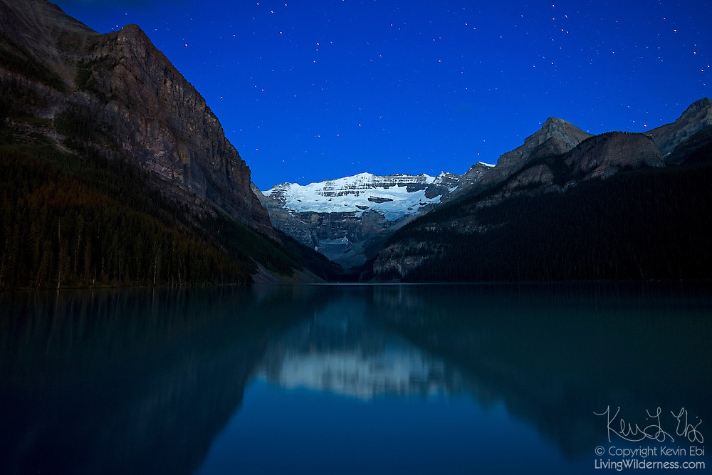 Stars are visible over the Canadian Rockies and Lake Louise about two hours before sunrise. Lake Louise is located in Banff National Park, Alberta, Canada.