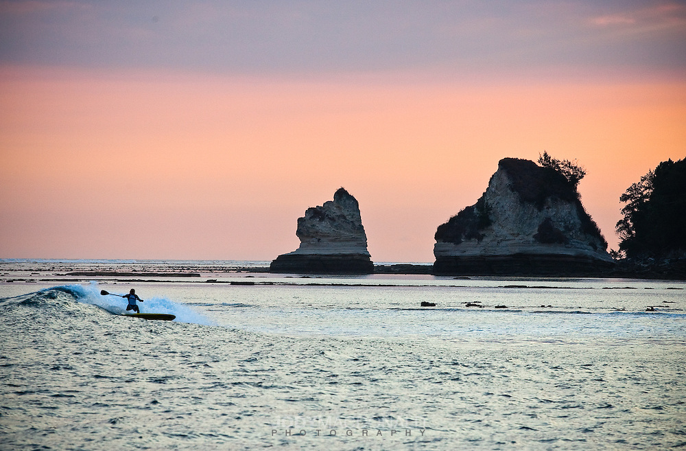 Surfer John Amundson rides one of his SUP boards at sunset on an unnamed break in Sumba, Indonesia.  Gorgeous sandstone rocks and reef set up a rather incredible backdrop.