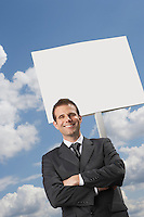 Businessman with arms crossed standing by blank sign against cloudy sky