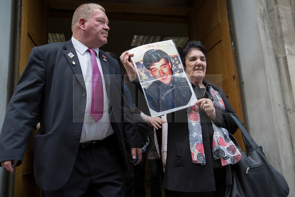 © licensed to London News Pictures. London, UK 25/04/2013. Teresa Glover holds up a picture of her son Ian, who died in Hillsborough disaster, outside the Family Division of the High Court in London as she and other families of victims attending a pre-inquest on Thursday, 25 April 2013. A hearing to decide the date and location of a new inquest into the 96 people who died in the Hillsborough disaster has begun in London. Photo credit: Tolga Akmen/LNP