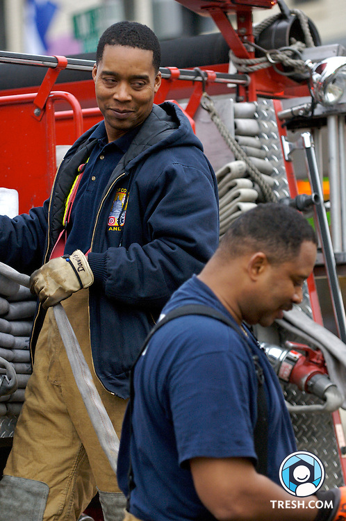 District of Columbia firefighter George Davis and Captain Kyle Gans pack equipment after being called to fight a fire in two roughly 150-square-foot rooms of the basement parking garage of Lofts 11, a condominium building under construction at 1123 11th Street, NW, in Washington D.C. Neighbors who smelled smoke called for firefighters, who located the source. The building was empty. Source: Battalion Fire Chief C.C. Diggs