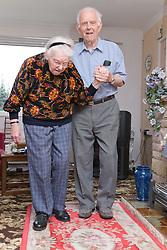 Elderly Carer helping wife with Alzheimer's disease to walk across the living room,