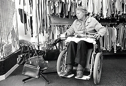 Elderly woman in wheelchair in charity shop, Nottingham UK 1989