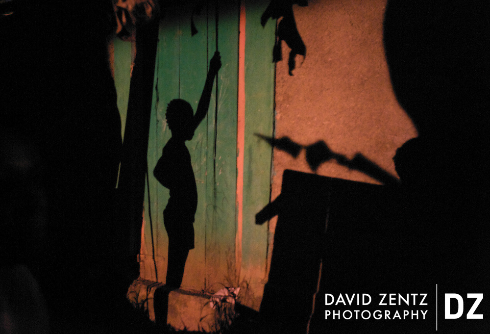 The shadow of a young girl is cast on the colorful wall of a home in Ville Bonheur, Haiti on July 16, 2008. The remote village plays host to thousands for 3 days each July during the Saut D'eau voodoo festival centered around the nearby Saut D'eau waterfalls.