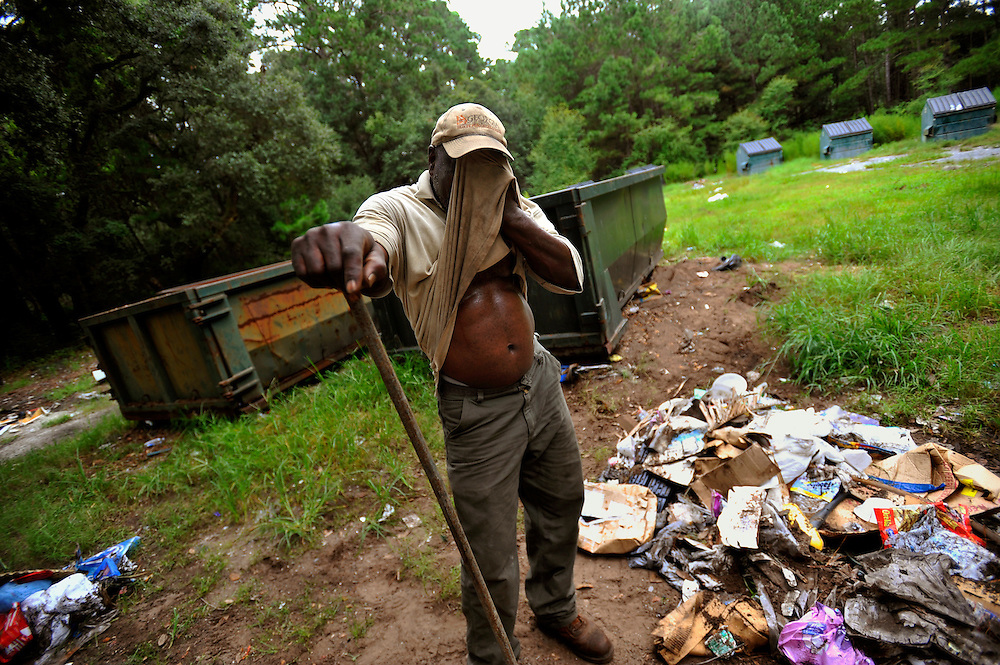 State of Georgia Department of Natural Resources employee Stanley Walker wipes his face while maintaining the trash dump on Sapelo Island, Ga. State employees and residents must haul their trash to the dump and maintain the site. Property owners are facing higher taxes, and fees from the county threatening an already fragile Geechee-Gullah community of Hog Hammock. (Stephen Morton for The New York Times)