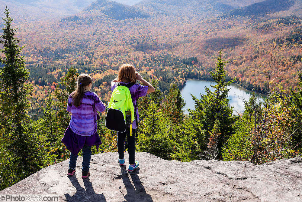 Hike Mount Jo in the Adirondack Mountains, near Lake Placid, North Elba, New York, USA. Beautiful Heart Lake and Adirondak Loj (an historic lodge) lie at the foot of Mount Jo (2876 ft or 877 m elev), which is on land owned by the Adirondack Mountain Club (AMC). With a sweeping vista of the Great Range, Mt Jo offers one of the best views for the effort in the Adirondacks: ascend 710 feet or 216 m from the Loj in 2.6 miles roundtrip. From atop Mt. Jo, see the surrounding High Peaks Wilderness Area, a state Forest Preserve protected within Adirondack Park. Adirondack Park is the largest park in the contiguous USA and is the largest National Historic Landmark. Geologic history: The Adirondacks are very new mountains from old rocks, uplifting in a circular dome (160 miles wide and 1 mile high) over just the past 5 million years. Geologically, the Adirondacks are NOT in the Appalachians: instead, they are part of the Canadian Shield (or Laurentian or Precambrian Shield which underlies half of Canada). The Adirondacks are still rising fast, up to 3 mm per year, with a central core (High Peaks region) of intrusive igneous rock, Anorthosite (not common at Earth's surface but common on the Moon's surface), surrounded by a massive dome of 1-billion-year-old metamorphic gneiss rock, in turn surrounded by some younger sedimentary rocks. In contrast, the unrelated Appalachians have mostly younger sedimentary rocks, yet are among the world's oldest mountains and are no longer uplifting.