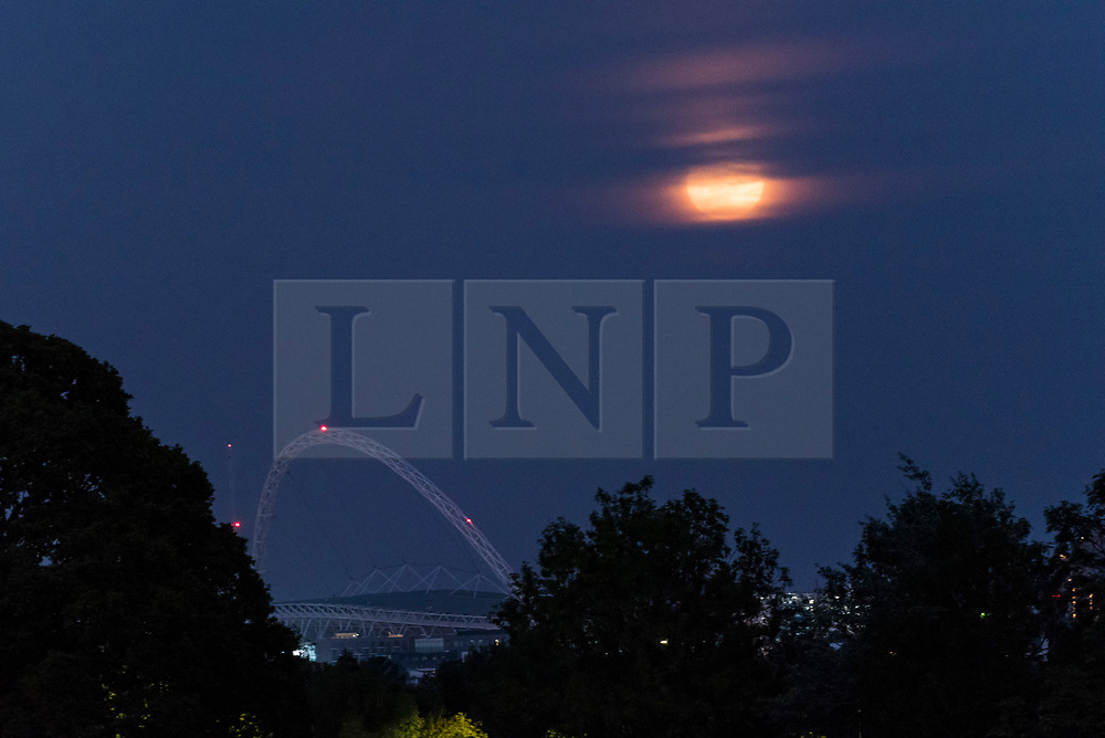 """© Licensed to London News Pictures. 07/05/2020. LONDON, UK.  A full moon, known this month as a Flower moon (named for the arrival of flowers in bloom in May), rises behind the arch of Wembley Stadium in north west London.  It is also the last """"supermoon"""" to be seen in 2020, where the moon is closest to the earth (the perigee) and appears 6% larger than a normal full moon.  Wembley Stadium is under consideration to be a neutral venue to host Premier League games as part of Project Restart in order for the football season to reach a conclusion after being suspended due to the ongoing coronavirus pandemic.  Photo credit: Stephen Chung/LNP"""