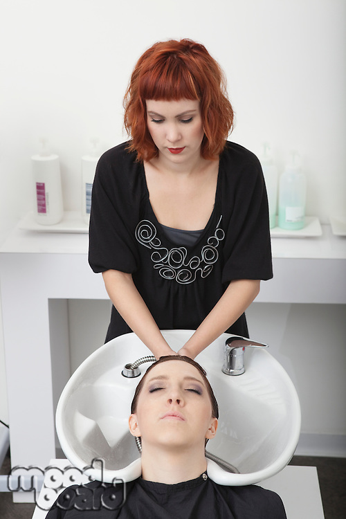 Hairdresser shampooing female client in salon basin