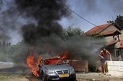 An Israeli man nearby a  burning  carafter it was hit by a katushya rocket fired by Hizbollah guerillas in Kiryat Shmona August 4, 2006. Two people were killed  by the rocket attacks and two Israeli soldiers were killed in south Lebanon clashes.