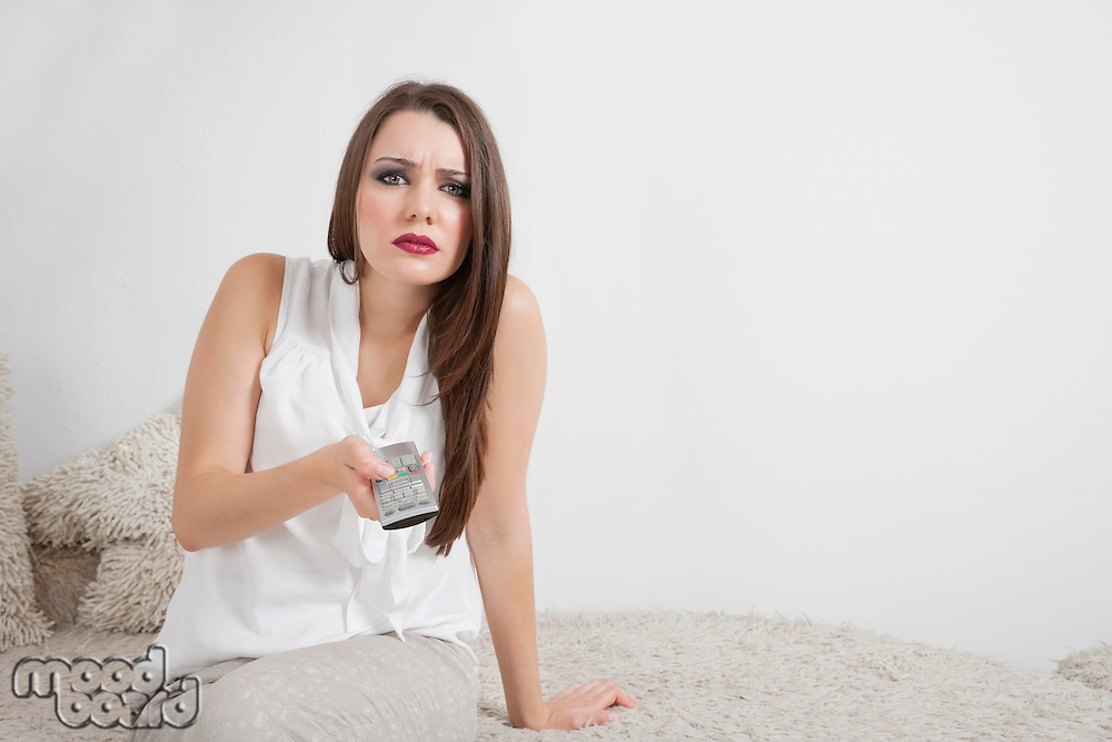 Portrait of beautiful young woman holding remote control