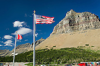 U.S. and Canadian Flags flying at Logan Pass Visitor center, Cloud formations, Glacier National Park Montana USA