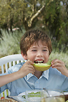 Portrait of boy (5-6) eating melon at garden table