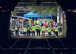 EDITOR'S NOTE: Photograph taken from a public area. © Licensed to London News Pictures. 09/11/2016. London, UK. Emergency workers inspect the track next to a derailed tram near Sandilands tram station in Croydon, Greater London. Dozens of people are believed to be injured with emergency services saying that there has been a number of fatalities. Photo credit: Peter Macdiarmid/LNP