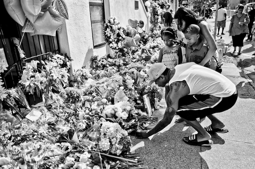 A man and his family light a candle at Emanuel AME Church in Charleston, South Carolina during a memorial for the 9 victims of the shooting at the church.
