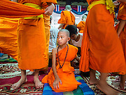"06 APRIL 2015 - CHIANG MAI, CHIANG MAI, THAILAND: A boy in his monk's robes sits on the floor while other boys put their robes on during the ordination on the last day of the three day long Poi Song Long Festival in Chiang Mai. The Poi Sang Long Festival (also called Poy Sang Long) is an ordination ceremony for Tai (also and commonly called Shan, though they prefer Tai) boys in the Shan State of Myanmar (Burma) and in Shan communities in western Thailand. Most Tai boys go into the monastery as novice monks at some point between the ages of seven and fourteen. This year seven boys were ordained at the Poi Sang Long ceremony at Wat Pa Pao in Chiang Mai. Poy Song Long is Tai (Shan) for ""Festival of the Jewel (or Crystal) Sons.   PHOTO BY JACK KURTZ"