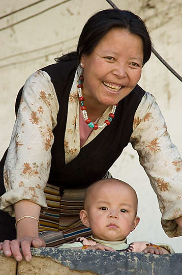 Mother with young child watch from balcony. Lhasa, Tibet. Asia.