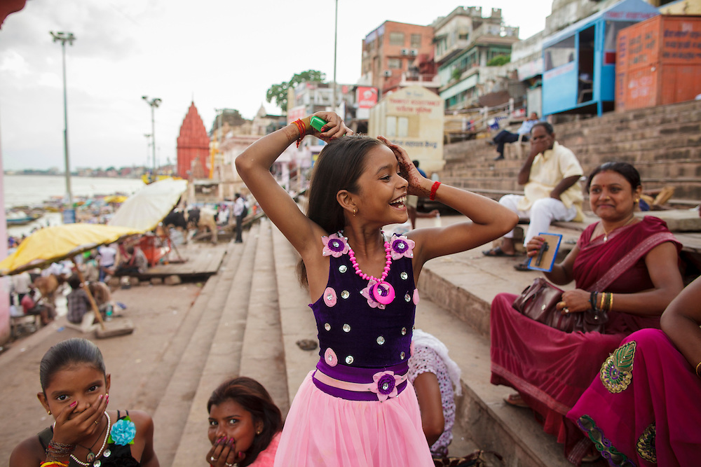 A young girl combing her hair at Dashashwamedh Gath near Ganges river  in Varanasi, India.