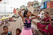 A young girl combing her hair at Dashashwamedh Gath near Ganges river  in Varanasi, India.