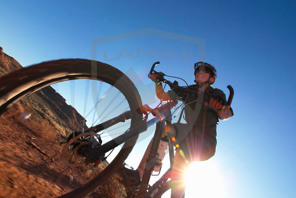 outdoor sports, recreation, travel, and adventure: smiling woman mountain biking with sun (sunshine lens flare), white rim trail, canyonlands national park, utah, horizontal, wide angle, low angle, copy space