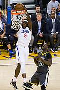 LA Clippers forward Montrezl Harrell (5) dunks the ball over Golden State Warriors forward Draymond Green (23) at Oracle Arena in Oakland, California, on February 22, 2018. (Stan Olszewski/Special to S.F. Examiner)
