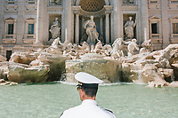 """ROME, ITALY - 20 JUNE 2017: A Roman policeman, entrusted to protect the Fountain of Trevi, is seen here by the fountain in Rome, Italy, on June 20th 2017.<br /> <br /> The warm weather has brought a menacing whiff of tourists behaving badly in Rome. On April 12, a man went skinny-dipping in the Trevi fountain resulting in a viral web video and a 500 euro fine.<br /> <br /> Virginia Raggi, the mayor of Rome and a national figurehead of the anti-establishment Five Star Movement,  issued an ordinance involving harsher fines for eating, drinking or sitting on the fountains, for washing animals or clothes in the fountain water or for throwing anything other than coins into the water of the Trevi Fountain, Bernini's Four Fountains and 35 other city fountains of artistic or historic significance around the city.  """"It is unacceptable that someone use them to go swimming or clean themselves, it's an historic patrimony that we must safeguard,"""" Ms. Raggi said."""