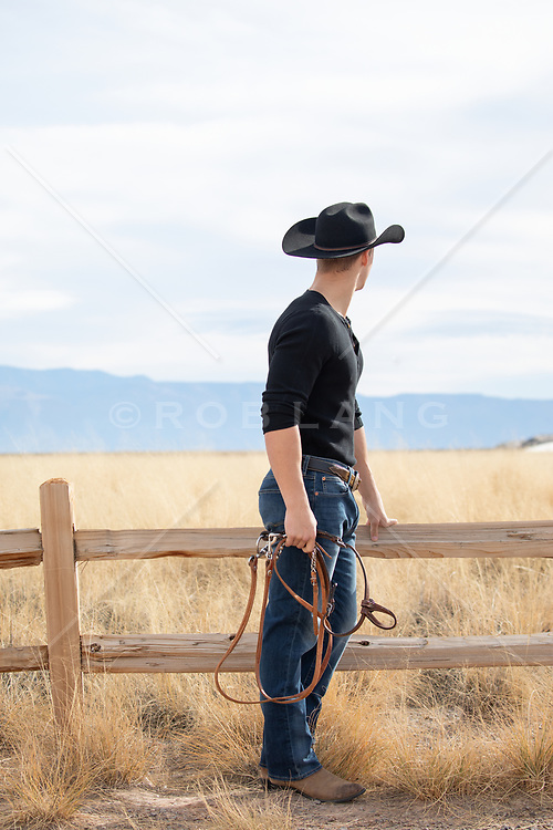 sexy young cowboy on a rustic ranch